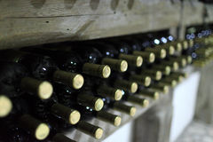 Botellas viejas de vino en un estante de madera Fotografía de archivo libre de regalías