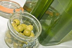 Botellas y aceitunas verdes Imagen de archivo