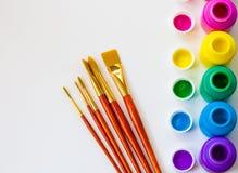 Botellas y brochas coloridas de la pintura en el fondo blanco con el espacio de la copia, la visión superior/artes y concepto del foto de archivo