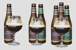 Botellas y vidrio de cervezas de Bélgica Straffe Hendrik aislados en fondo ligero imagenes de archivo