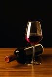 Botellas y vidrio de vino rojo en la tabla de madera y el fondo negro Imagen de archivo