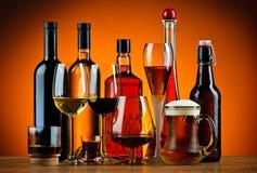 Botellas y vidrios de bebidas del alcohol Foto de archivo