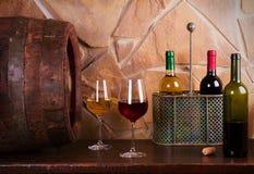 Botellas y vidrios de rojo y de blanco en la bodega, barril de vino viejo Foto de archivo libre de regalías