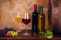 Botellas y vidrios de rojo y de blanco en la bodega, barril de vino viejo Imágenes de archivo libres de regalías