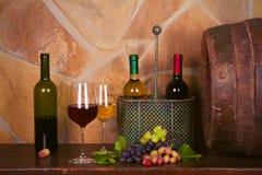 Botellas y vidrios de rojo y de blanco en la bodega, barril de vino viejo Fotografía de archivo