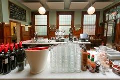 Botellas y vidrios de vino en contador del café artístico viejo con muebles antiguos y lámparas en estilo de la viejo-moda Fotografía de archivo libre de regalías