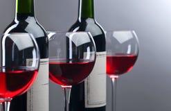 Botellas y vidrios de vino rojo Imagenes de archivo