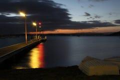 Boten in de kust van een meer in schemer Stock Afbeeldingen