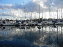 Boten in een haven op waterspiegel wordt weerspiegeld die stock foto's
