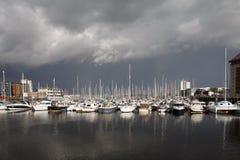 Boten in een jachthaven met stormachtige hemel stock foto's
