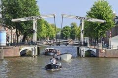Boten in een kanaal met Ophaalbrug in Amsterdam. Stock Foto