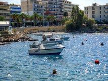 Boten en een klein strand op de dijk van de toeristenstad van Loutraki stock foto's