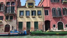 Boten en het voortbouwen op waterkanaal in Venetië stock footage