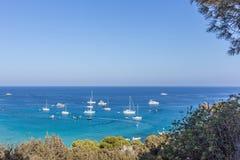 Boten en jachten die dicht bij de overzeese kust in blauwe lagune worden verankerd Royalty-vrije Stock Afbeeldingen