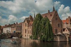 Boten en oude gebouwen op de kanaal` s rand in Brugge Stock Foto's