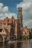 Boten en oude gebouwen op de kanaal` s rand in Brugge Stock Foto