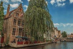 Boten en oude gebouwen op de kanaal` s rand in Brugge Stock Fotografie