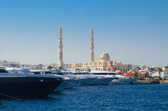 Boten in haven naast de visserijmarkt en Centrale Moskee op de achtergrond Stock Afbeeldingen