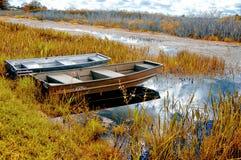 Boten op de herfst van de rivierkust in de moerassen stock foto