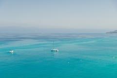 Boten op het glasheldere overzees dichtbij de stad van Tropea-gebied Calabrië Stock Fotografie