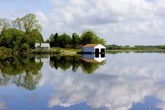 Botenhuis dat in rivier wordt weerspiegeld stock afbeelding