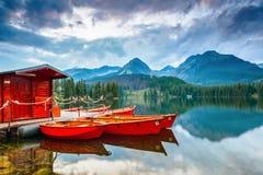 Botentribune dichtbij houten brug en een hut op een bergmeer Stock Fotografie