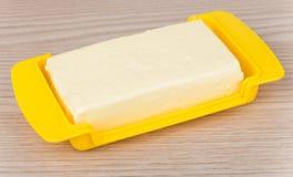 Boter in gele plastic schotel op lijst Royalty-vrije Stock Foto
