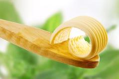 Boter krul op een houten lepel stock afbeelding