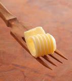 Boter krul op een houten vork stock afbeelding