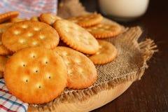 Boter van de koekjescracker en melk opstelling op servet en houten bac Stock Afbeeldingen