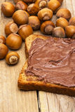 Boterham met chocolade met hazelnoten op hout royalty-vrije stock afbeeldingen
