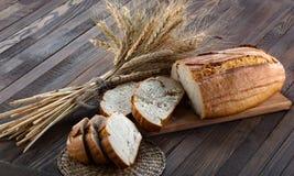 Boterhammen op een scherpe raad en oren van tarwe op het hout Stock Foto