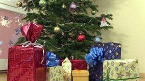 Boîtes colorées de présent de cadeau avec le ruban sous l'arbre de Noël banque de vidéos