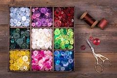 Botões coloridos com agulha, linha e tesouras Fotografia de Stock