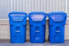 Botes de basura azules contra una pared imagenes de archivo