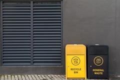 Botes de basura contra la pared oscura en zona urbana imagen de archivo
