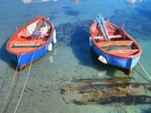 Botes de remos coloreados en el mar claro. Foto de archivo