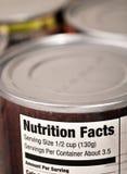 Boîtes en fer blanc de nourriture avec l'étiquette de faits de nutrition Photos libres de droits