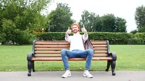 Both Hands Thumbs Up by Man Sitting on Bench in Park, Red Hairs and Beard. 4k , high quality stock video footage