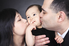 Both kiss baby Stock Photo