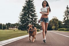 We both need some exercise!. Full length of beautiful young woman running with her dog through the park and smiling while spending time outdoors Stock Images