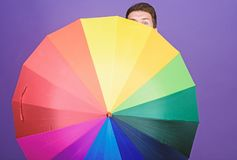 For both rainy and sunny day. Homosexual man holding colorful umbrella. Gay with open folding umbrella. Fashion man with. Colorful accessory. Mens rain gear stock image