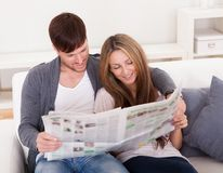 Both read article from newspaper Stock Images