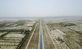 The highway is lined with plants on both sides of the highway. Stock Images