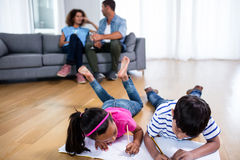 Bother and sister lying on floor and studying Royalty Free Stock Image