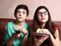 Bother and sister watch movie with remote Royalty Free Stock Image