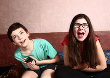 Bother and sister watch movie with remote Stock Photography