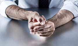 Bothered businessman hands holding fingers with tension expressing controlled exasperation. Closeup of bothered businessman hands holding fingers with tension Stock Image