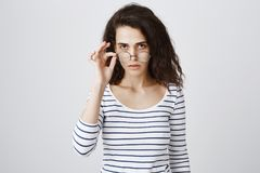 Bothered girl has no idea why person talking to her. Portrait of annoyed and tired smart curly-haired woman taking off. Glasses and looking from under forehead stock photography