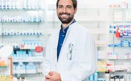 Boticario en la farmacia que se coloca en el estante con las drogas imagen de archivo libre de regalías